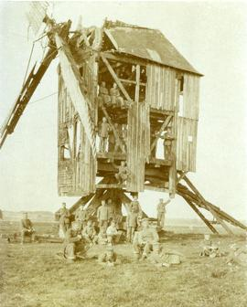 Soldiers pose inside and around a destroyed post mill