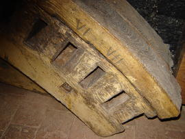 Section of old brakewheel, with Roman numerals marking cogs removable for engine drive, smock mil...