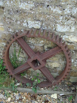 Displaced iron gearwheel leaning against outside of tower, Great Mill, Haddenham