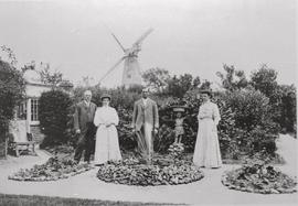Group of people posing in a garden with Richardson's Mill, Boughton Street behind
