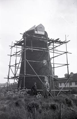 """Windmill surrounded by scaffolding, Mr & Mrs H.E.S Simmons standing in front of mill, A..."