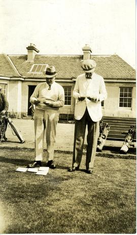Two men inspecting cards before golf