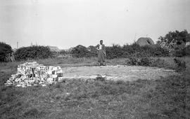 """H.E.S. Simmons looking at remains, site of windmill at Bodle Street Green, Sussex"""