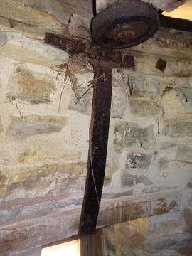 Truck wheel and iron strap, purpose unknown, in tower wall, Stembridge Mill, High Ham