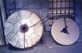 Photograph of two French millstones against a wall
