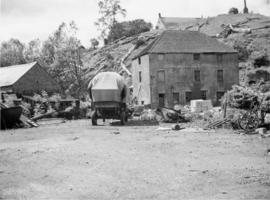 View of Mill and surrounding buildings with farm machinery
