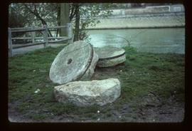Pair of millstones lying by river