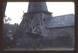 Cap of preserved smock mill being raised from/lowered to ground by crane