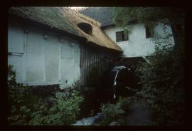 Exterior of thatched/half-timbered watermill building with wheel