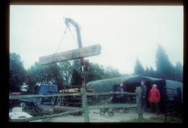 Crane lifting item of timber onto flatbed truck