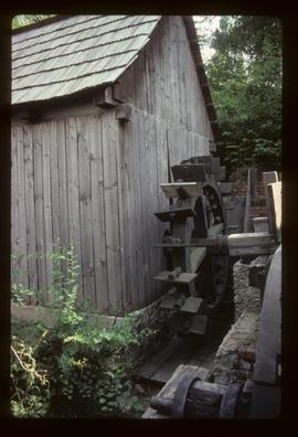 Exterior of preserved watermill building with wheel