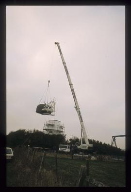 Cap and fan assembly being lifted off ground by crane, Waterhall Mill, Patcham