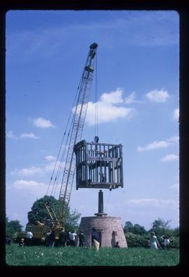 Buck frame being lifted onto top of post by crane