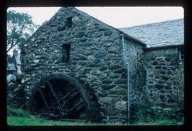 Exterior of stone watermill building with wheel