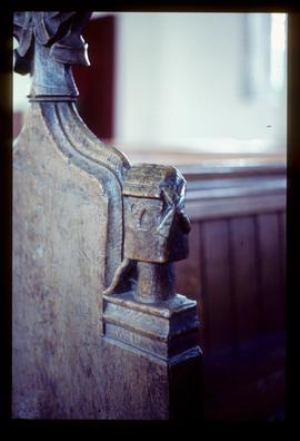 Carving of post mill on bench end in church