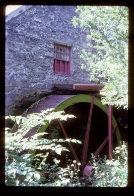 Part of exterior of preserved watermill building showing wheel