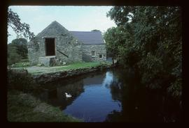 Exterior of watermill building by pond