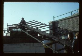Four men preparing new sail for lifting into position, Ashby's Mill, Brixton