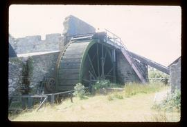 derelict watermill building with surviving wheel and associated gearing