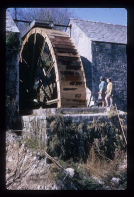 Exterior view of pair of stone watermill buildings with single very large wheel between them