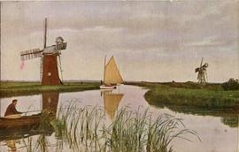 View of windpumps with boats on river