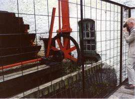 Photograph of Niall Roberts photographing waterwheel gearing, Kilbeggan Distillery, Westmeath, Ir...