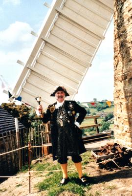 Belper Town Cryer poses by sail of Heage Tower Mill
