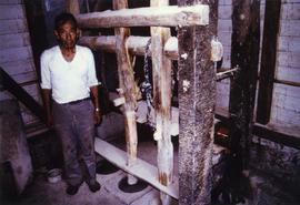 Photograph of a Japanese man next to mill machinery