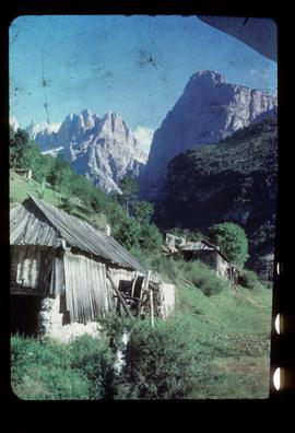 Pair of small derelict watermill buildings with mountains in background