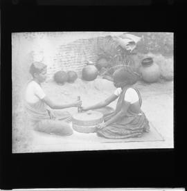 Two women operating hand quern