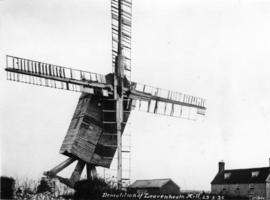 Post mill, Leavenheath, at moment of demolition, complete with sails
