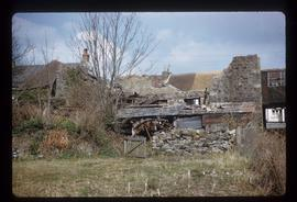 Partly demolished stone watermill building with wheel