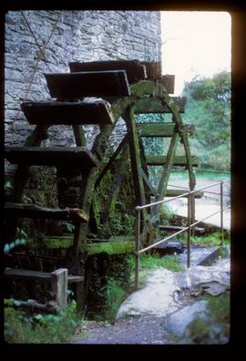 Part of exterior of watermill building showing derelict wheel