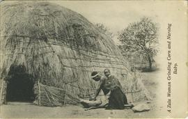 A Zulu woman grinding corn and nursing a baby