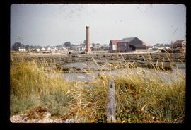 Mid-distant view of large watermill building with tall chimney nearby