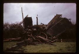 Preserved post mill with sails, with wreckage of collapsed smock mill in foreground