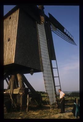 Man setting cloths on sails of restored open-trestle post mill