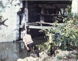 Photograph of Niall Roberts looking at a waterwheel, France