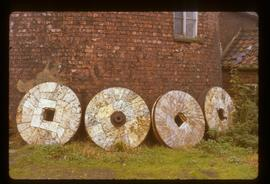 Four millstones lying against wall of tower mill