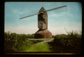 Colourised photo/postcard showing derelict post mill with two sails