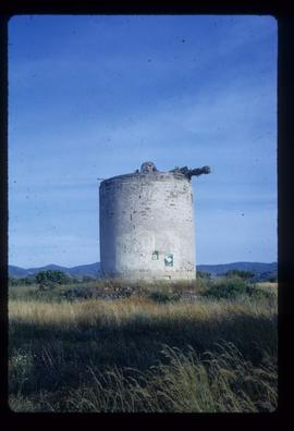 Derelict parallel-sided tower mill with windshaft, brakewheel and wooden poll end