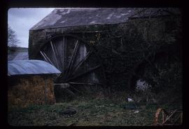 Exterior view of stone watermill building with wheel