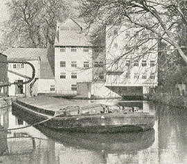"""Sonning mill, with a covered Thames barge moored alongside """